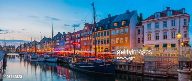 copenhagen nyhavn colorful harbour bars restaurants illuminated sunset panorama denmark - nyhavn stock pictures, royalty-free photos & images