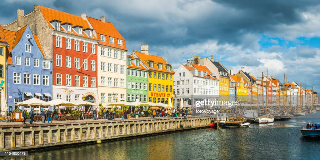 Copenhagen Nyhavn colourful bars restaurants crowded harbour quayside panorama Denmark : Stock Photo