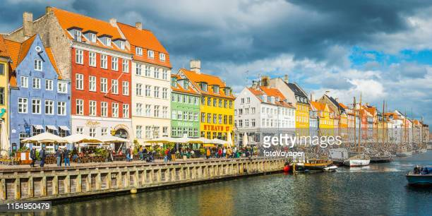 copenhagen nyhavn colourful bars restaurants crowded harbour quayside panorama denmark - nyhavn stock pictures, royalty-free photos & images