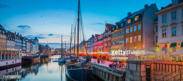 copenhagen nyhavn harbour restaurants cafes warmly illuminated sunset panorama denmark - copenhagen stock pictures, royalty-free photos & images