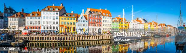 copenhagen nyhavn panorama city crowds enjoying sunshine restaurants bars denmark - copenhagen stock pictures, royalty-free photos & images