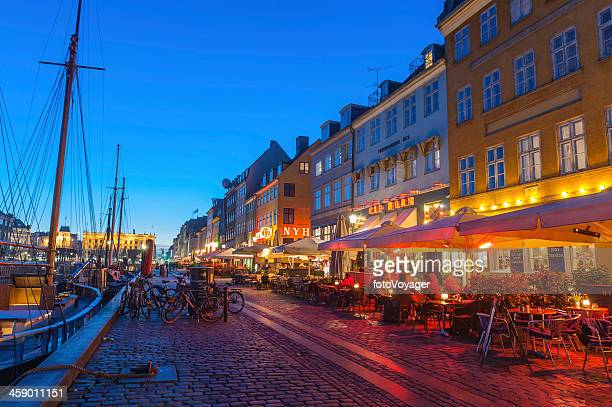 copenhagen nyhavn restaurants illuminated at dusk denmark - nyhavn stock pictures, royalty-free photos & images