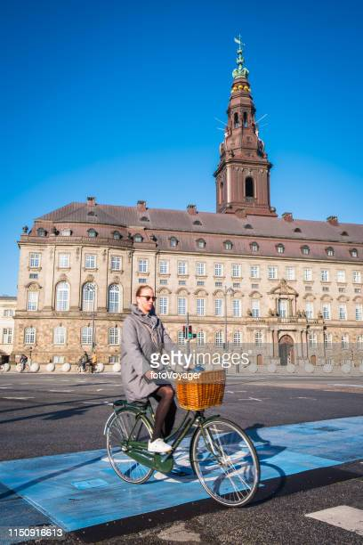 copenhagen woman cyclist riding bike below christiansborg slot parliament denmark - christiansborg palace stock pictures, royalty-free photos & images