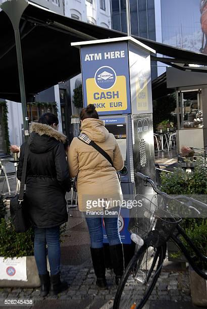 Copenhagen/Denmark/ _ 17th November 2015_Female tourists cashing money at atm on streoget