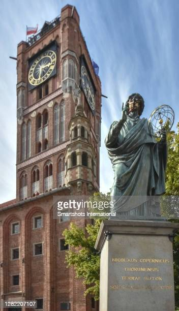 copernicus statue with torun's town hall clock tower on background in torun, poland - 名作 発祥の地 ストックフォトと画像