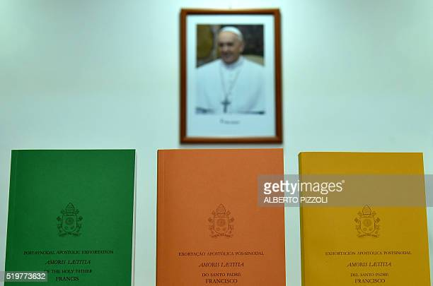 Copies of a postsynodal apostolic new guideline on a range of issues related to the family are pictured near a photograph of the Pope on April 8 2016...