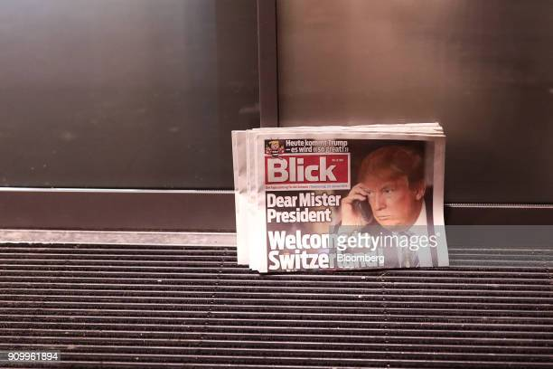 Copies of the Blick newspaper featuring a picture of US President Donald Trump and the headline 'Welcome to Switzerland' stand outside the entrance...