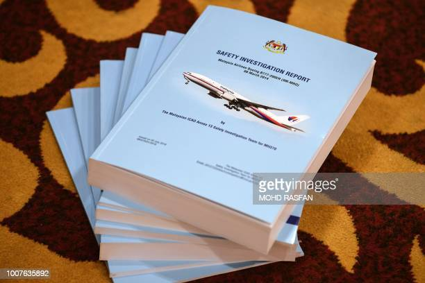 Copies of the MH370 safety investigations report are seen on the floor during a media briefing in Putrajaya outside Kuala Lumpur on July 30 2018...