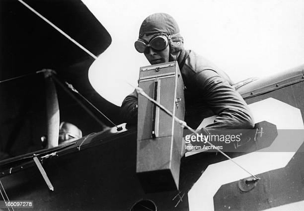 Co-pilot aims a pistol-grip camera over the side of an airplane during World War I, late 1910s.