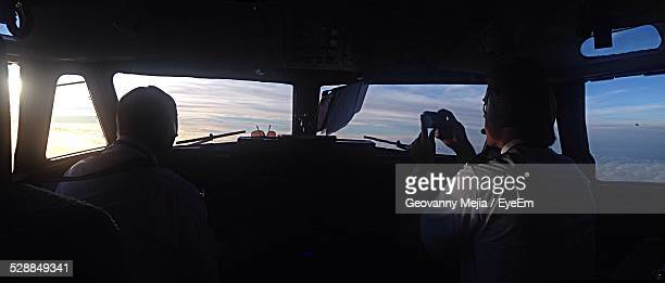co-pilot taking picture of sunset in cockpit - co pilot stock photos and pictures