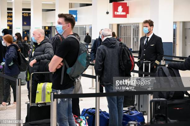 Co-pilot wearing PPE , including a face mask as a precautionary measure against COVID-19, queues at a check-in desk at Manchester Airport in northern...