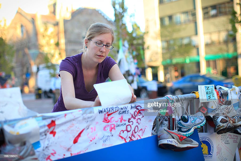 """Copley Square - Marta Crilly, of Dorchester, an assistant archivist at Boston's Office of City Clerk Archives and Records Management Division, works carefully to separate hand-written paper signs and mementos from other objects left at the Copley Square Boston Marathon memorial. Workers from the Boston City Archives and Mayor Menino's office culled through the makeshift memorial to the Boston Marathon bombings in Copley Square early on Tuesday morning, May 7, 2013 to remove handwritten signs, posters, notes, and other fragile items so the keepsakes can be preserved. Weather forecasters expect rain on Wednesday and through the rest of the week. City officials want to save the paper items before rain blurs the ink and disintegrates the paper. """"We want to get all the paper out of there to ensure the rain doesn't destroy it,"""" John McColgan, the Boston City Archivist."""" The first step is to ensure that the hardcopy is preserved and it is documented."""