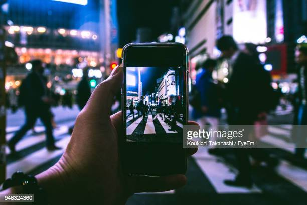 Copped Hand Of Person Photographing Crowd On Zebra Crossing At Night