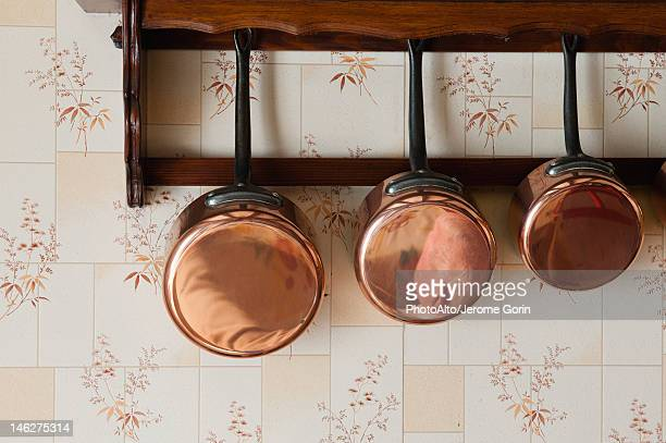 Copper pots hanging on wall rack