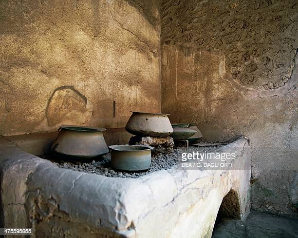 Copper pots on the stove in a kitchen House of the Vettii Pompeii Campania Italy Roman civilisation 1st century