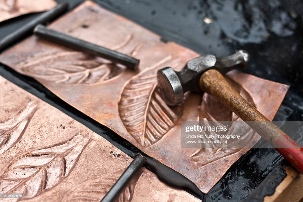 Coppersmith tools and copper sheets with leaves : Photo