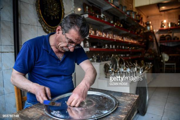 A coppersmith works on the decorations of a metal tray in his workshop in the historical part of Gaziantep city on May 2 southeastern Turkey
