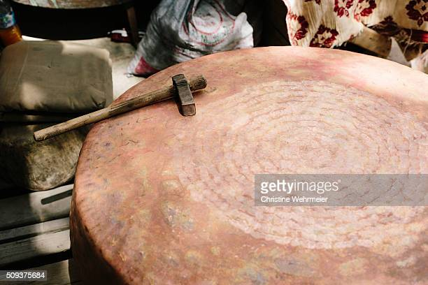 coppersmiths hammer resting on a large pan. place seffarine, fez, morocco - christine wehrmeier stock photos and pictures