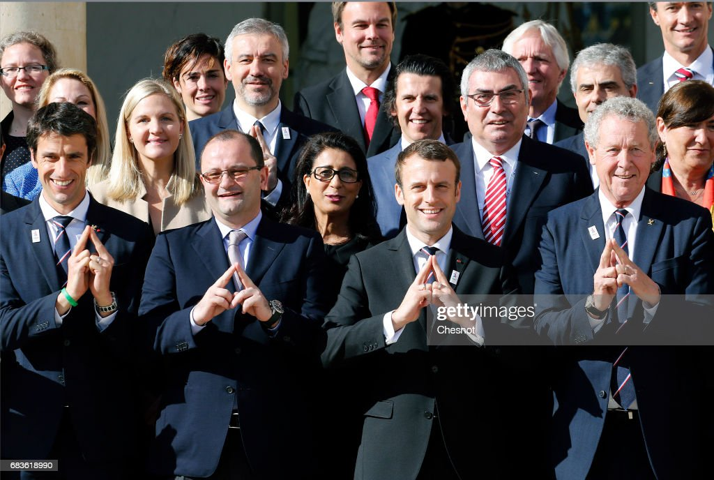 Co-president of Paris 2024 bid Tony Estanguet, International Olympic Committee Evaluation Commission Chair, Patrick Baumann, new French President Emmanuel Macron and member of the IOC Guy Drut make a sign representing the Eiffel Tower, the logo of Paris 2024 bid as they pose members of the International Olympic Committee (IOC) Evaluation Commission during a family photo at the Elysee Presidential Palace in Paris, France, May 16, 2017. The cities of Paris and Los Angeles are currently bidding to host the 2024 Olympic Game