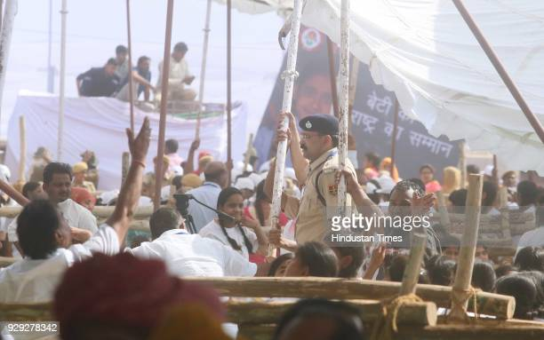 Cops come to rescue as a sand storm blows the tent away during Prime Minister Narendra Modi's public rally at the launch of National Nutrition...