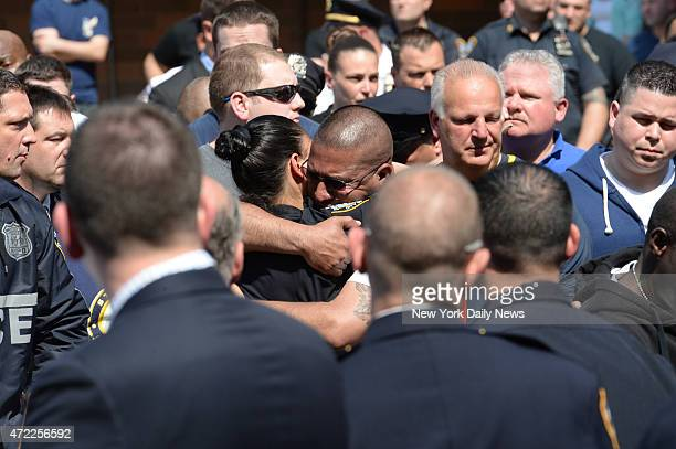 Cops hug as the body of Police Officer Brian Moore leaves Jamaica Hospital He was shot in the face two days agoallegedly by Demetrius Blackwell who...