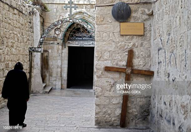 Coptic Christian monk walks past a cross on the roof of the Church of the Holy Sepulture in Jerusalem's Old City on October 20, 2018.