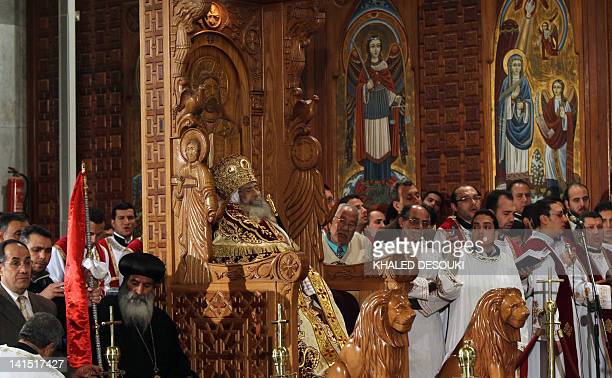 Coptic Christian mourn the death of Pope Shenuda III the spiritual leader of the Middle East's largest Christian minority who is sitting dressed in...
