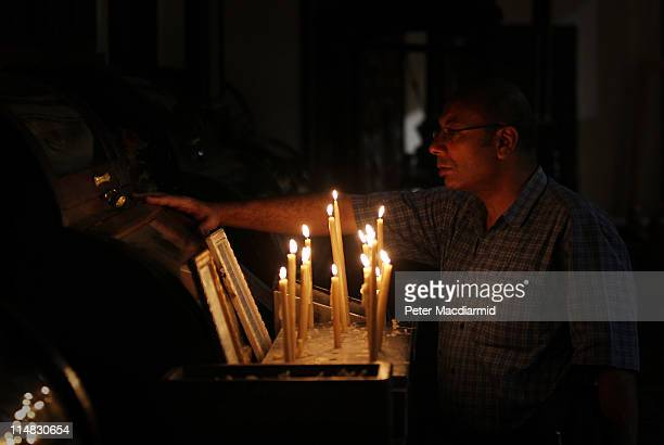 Coptic Christian stands near candles in The Hanging Church on May 27 2011 in Coptic Cairo Egypt Protests in January and February brought an end to 30...