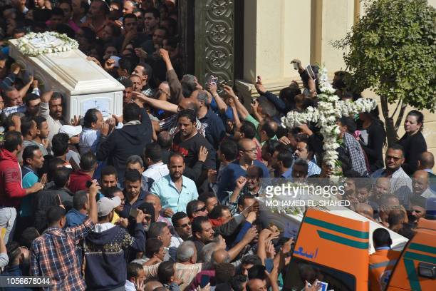 Coptic Christians carry the coffins of victims killed in an attack a day earlierfollowing a morning ceremony at the Prince Tadros church in Egypt's...