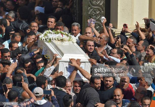 TOPSHOT Coptic Christians carry the coffins of victims killed in an attack a day earlierfollowing a morning ceremony at the Prince Tadros church in...