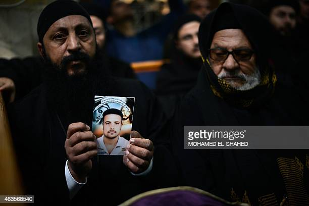 A Coptic clergyman shows a picture of a man whom he says is one of the Egyptian Coptic Christians purportedly murdered by Islamic State group...