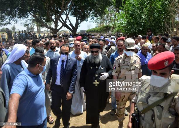 Coptic Orthodox Christian priest walks with other officials at a procession during the funeral of Egyptian soldier Alaa Emad in the village of Sbwan...