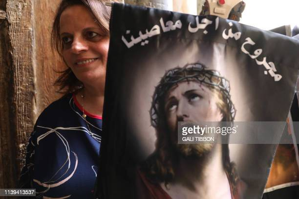 Coptic Orthodox pilgrim, carrying a cross and a banner with the face of Jesus along the Via Dolorosa , enters the church of the Holy Sepulchre in...