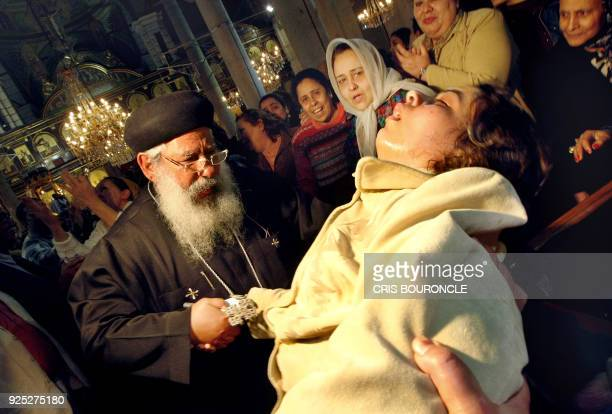 Coptic priest Father Makari attends to a woman said to be 'under the power of a spell' during a mass at St Mark's church in Cairo on February 29 2008...