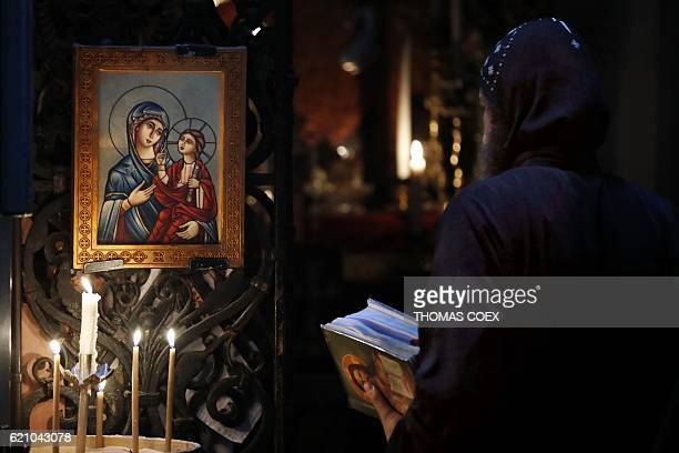 A Coptic priest prays in front of a Christian Icon featuring the Virgin Mary on November 4 2016 at the Church of the Holy Sepulchre in Jerusalem's...