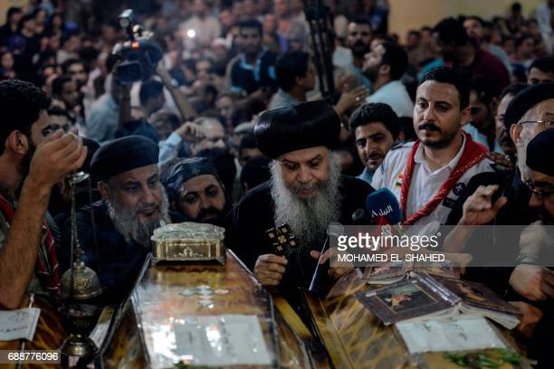 Coptic priest speaks on a microphone as relatives of killed Coptic Christians grieve during the funeral at Abu Garnous Cathedral in the north Minya...