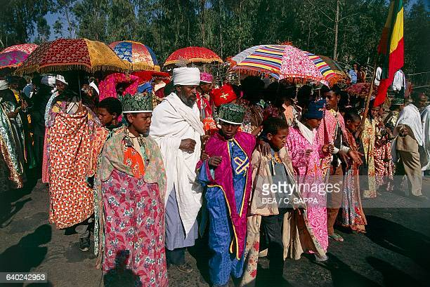 Coptic priests shading themselves under umbrellas during a procession for the Timkat festival Coptic Epiphany Gondar Ethiopia