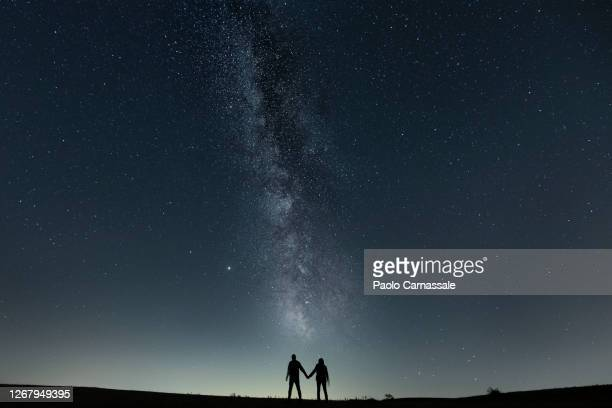copule holding hands under milky way - star field stock pictures, royalty-free photos & images