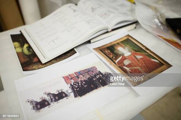 A copy of a painting of the funeral precession of Elizabeth I is seen as members of the conservation team fit a 'pair of straight bodies' to the...