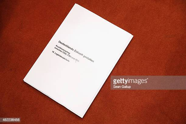 A copy of the 177page threeparty coalition contract lies on the ground shortly after German Chancellor and Chairwoman of the German Christian...