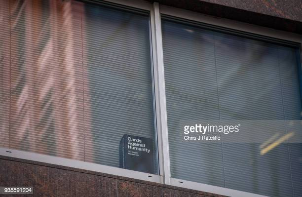 A copy of the game 'Cards Against Humanity' is seen in a the window of the floor occupied by company Cambridge Analytica on March 21 2018 in London...
