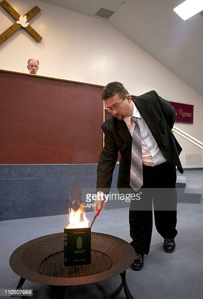 RELIGIONA copy of the Holy Koran is set on fire by pastor Wayne Sapp as Terry Jones looks on March 20 2011 at the Dove World Outreach Center in...