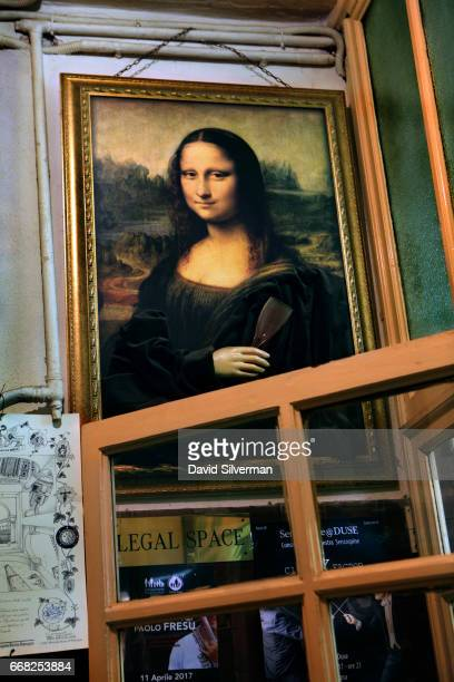A copy of the Mona Lisa holding a wine glass is hung above the entrance at the Osteria Del Sole bar on March 30 2017 in Bologna Italy Situated on Via...