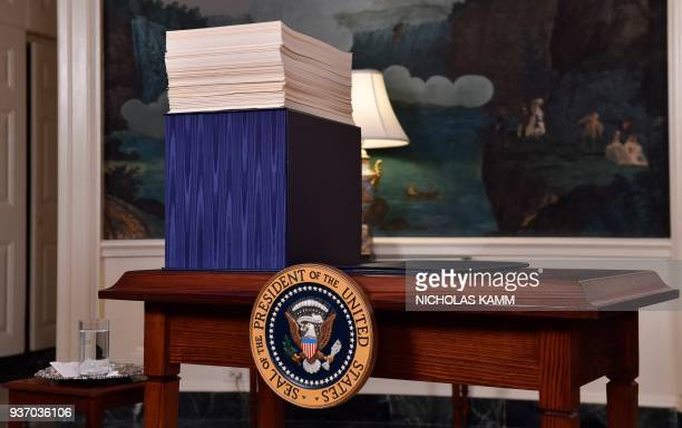 Copy of the spending bill, approved by Congress, is seen on a desk before US President Donald Trump speaks about the bill in the Diplomatic Room at...