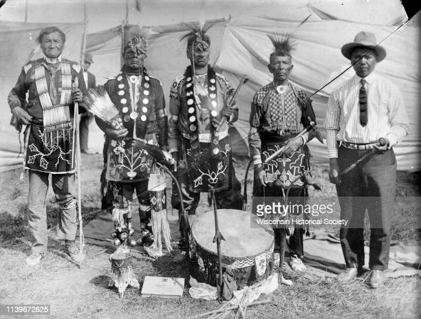 Copy photograph of five HoChunk men posed standing behind a Dream Drum in front of cloth barriers or tents Black River Falls Wisconsin 1908 A powwow...