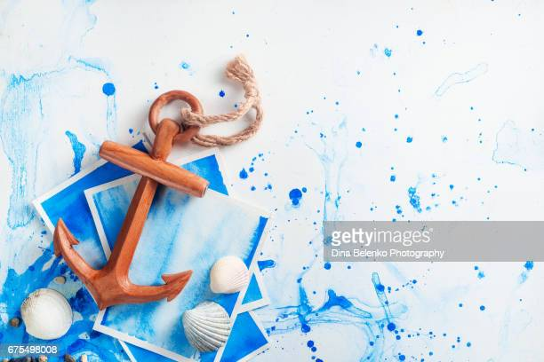 Copy space travel background with wooden anchor and seashells
