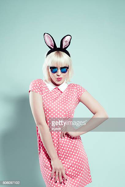 Coquettish blonde young woman wearing rabbit ears headband and sunglasses
