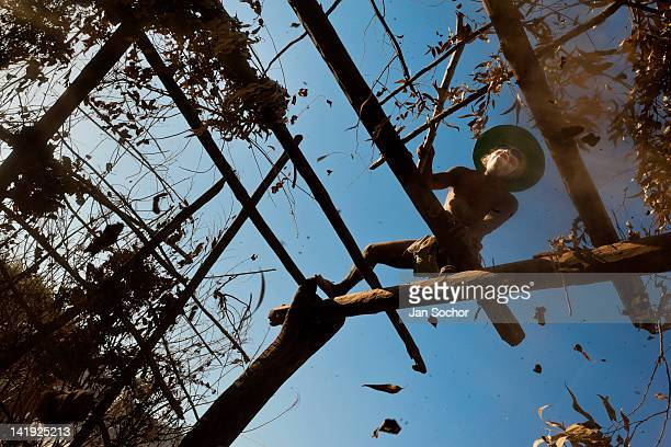 "Cora Indian man dismantles ""ramada"", a temporal shack made from branches, at the end of the Semana Santa celebration in Jesús María, Nayarit, Mexico,..."