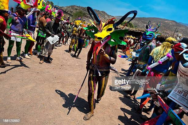 Cora Indian man, wearing a scary colorful demon mask, walks in a procession during the sacred ritual ceremony of Semana Santa in Jesús María,...