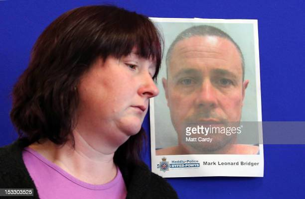 Coral Jones passes a poster showing the face of Mark Bridger as she prepares to speak at a DyfedPowys Police press conference and appeal for the...